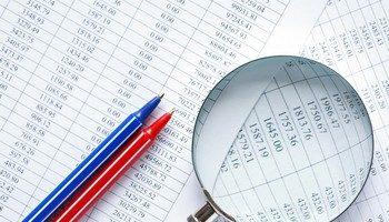 I nuovi limiti alle spese per la formazione dei professionisti rappresentati da una lente d'ingrandimento che analizza un report di spese